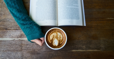 Canva - Person Having Cup of Latte While Reading Book